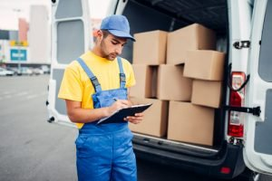Delivery worker takes inventory of credential clothes shipment