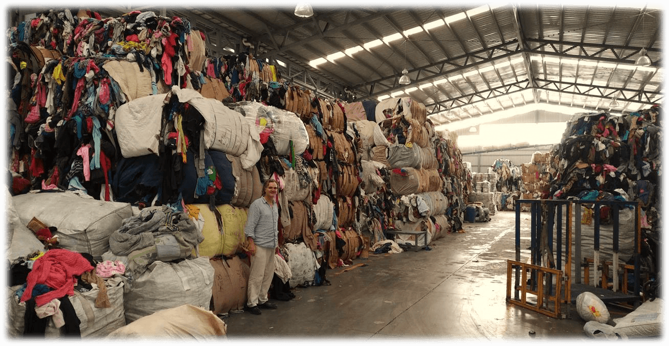 Man stands in full warehouse of used credential clothing