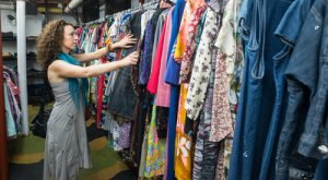 Woman browses vintage clothing for sale