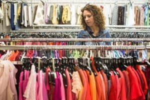 Woman browses racks of used clothing for sale Bank & Vogue