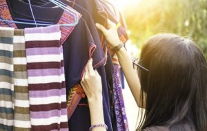 Woman inspects vintage clothing at thrift store