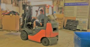 Man on forklift moves credential clothing in warehouse