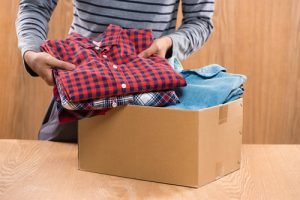 packing clothes into a box for donation