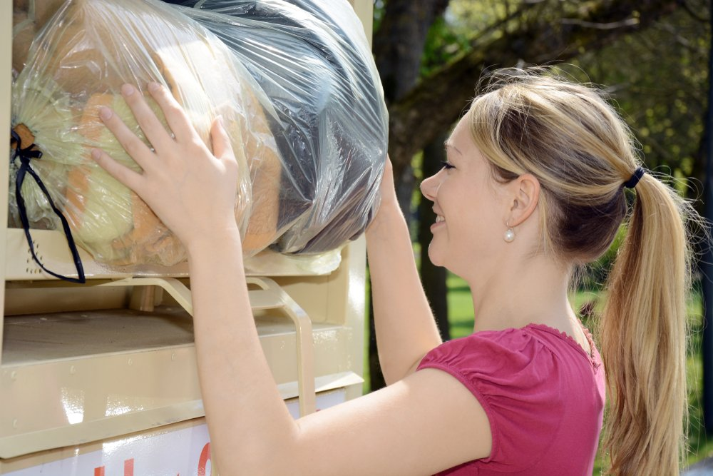 woman donating bag of used clothing into donation bin